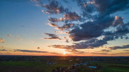 Aerial view of a Sunset over barns, silos and farmlands during the golden hour with blue sky, clouds and red sun 스톡 콘텐츠 - 147957421