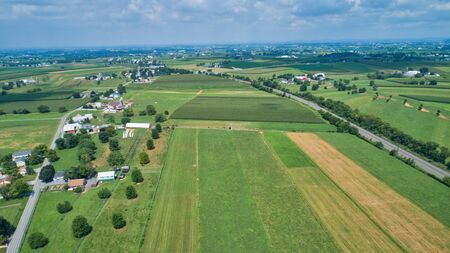 Aerial view of farm lands in summer with blue skies and white fluffy clouds