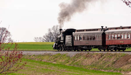 A beautiful shot of an antique steam train and passenger cars, puffing smoke thru countryside