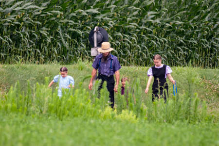 Ronks, Pennsylvania, July 2007 - Amish family, father and three daughters, walk along rail road tracks with dog on a sunny summer day 에디토리얼