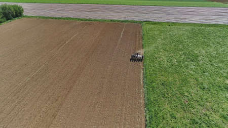 An aerial shot of donkeys pulling farming equipment 스톡 콘텐츠 - 150973338