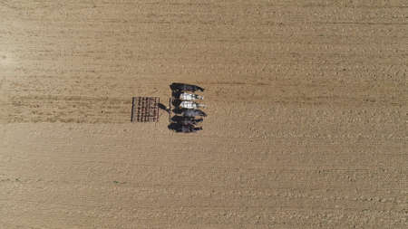 An aerial shot of donkeys pulling farming equipment 스톡 콘텐츠