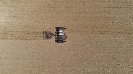 An aerial shot of donkeys pulling farming equipment 스톡 콘텐츠 - 150973340