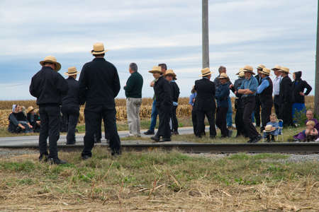Strasburg, Pennsylvania, October 2019 - Group of Amish men women and children patiently wait for a train to pass along train tracks on a fall day.