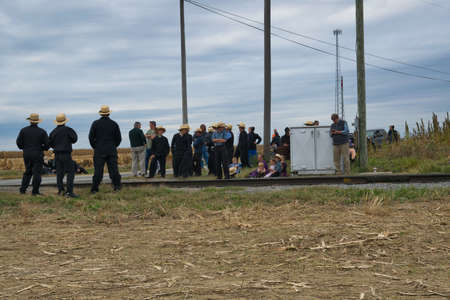 Strasburg, Pennsylvania, October 2019 - Group of Amish men women and children patiently wait for a train to pass along train tracks on a fall day. 스톡 콘텐츠 - 150897422