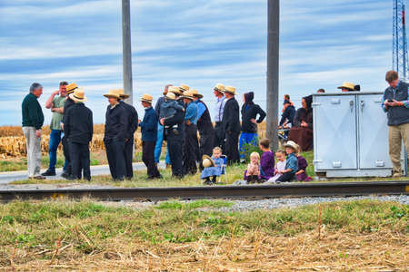 Strasburg, Pennsylvania, October 2019 - Group of Amish men women and children patiently wait for a train to pass along train tracks on a fall day. 스톡 콘텐츠 - 150897437