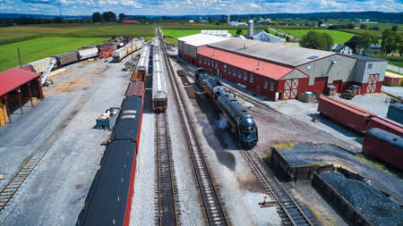 Aerial View of a Restored Antique Steam Engine Blowing Smoke and Steam in Freight Yard on a Sunny Day 免版税图像