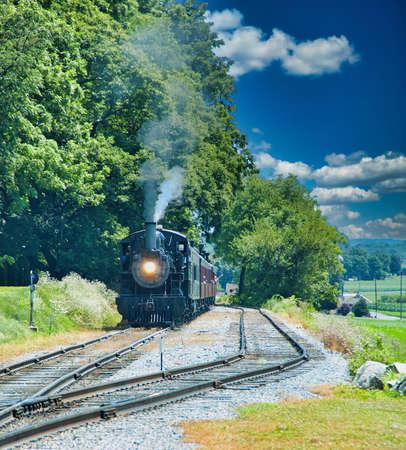 Restored Antique Steam Locomotive with Passenger Cars Steaming Up Foto de archivo