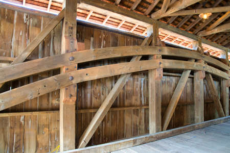 Close Up View of the Burr Arch Truss of a Restored Old 1844 Covered Bridge on a Sunny Day