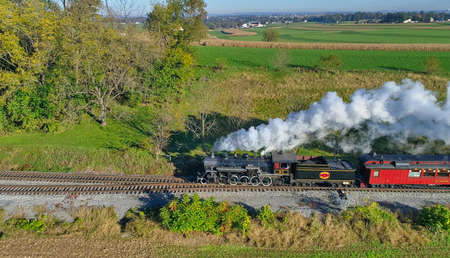 Strasburg, Pennsylvania, October 2020 - Aerial View of Steam Passenger Train Puffing Smoke Traveling in Amish Countryside in an Early Morning