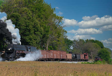 Strasburg, Pennsylvania, October 2019 - Antique Steam Freight Train Puffing Smoke and Steam While going Thru Amish Countryside