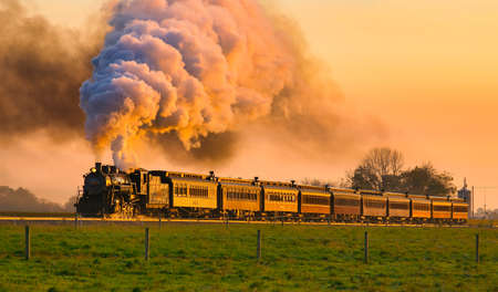 Strasburg, Pennsylvania, October 2020 - View of Golden Steam Passenger Train at Sunrise Traveling Thru Amish Countryside with lots of Smoke and Steam Editorial
