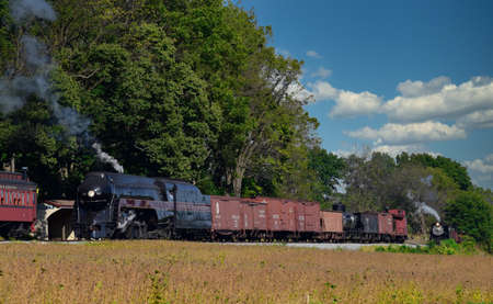 Strasburg, Pennsylvania, October 2019 - 2 Antique Steam Freight Train Puffing Smoke and Steam While going Thru Amish Countryside