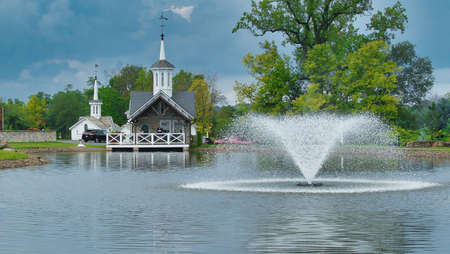 Old Restored White Barns with Cupolas and 5 Pointed Stars by a Pond with a Fountain Foto de archivo