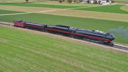 Aerial View of a Restored Antique Steam Locomotive Pulling a Caboose on a Sunny Fall Day 스톡 콘텐츠