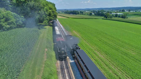 Aerial View of a Restored Antique Steam Engines and Passenger Cars Steaming Up at a Small Rail Road Station