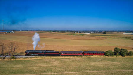 Aerial View of a Restored Antique Steam Locomotive Pulling Passenger Cars on a Sunny Fall Day