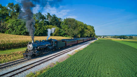 Aerial View of a Restored Antique Steam Engine and Passenger Cars Steaming Up at a Small Rail Road Station on a Summer Day