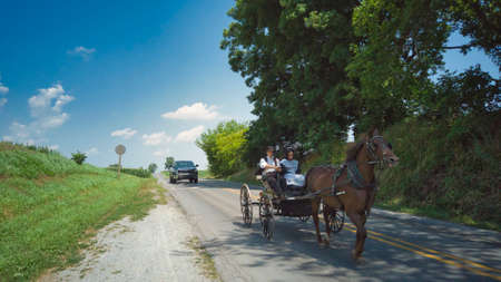 Ronks, Pennsylvania, July 2020 - An Amish Horse and Open Buggy With an Amish Couple in it on a Summer Day
