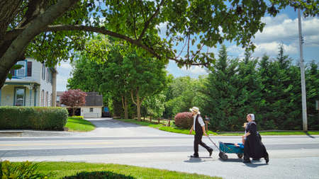 Gordonville, Pennsylvania, June 2020 -An Amish Family Walking along a Country Road Pulling a Wagon with a Small Child in it