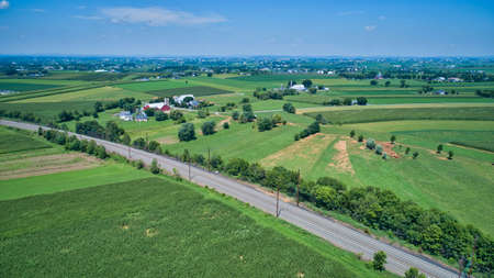 Aerial View of Multiple Farms and Train Tracks going Thru Them on a Beautiful Summer Day 스톡 콘텐츠