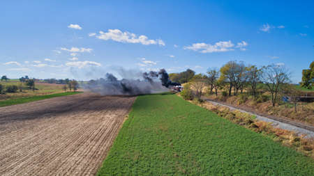 Aerial View of An Antique Restored Steam Locomotive Blowing Smoke and Steam Traveling Thru Farmlands and Countryside on a Sunny Summer Day 스톡 콘텐츠