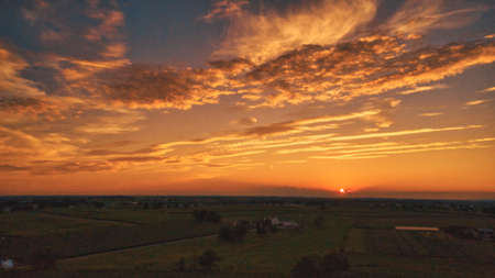 An Aerial View of a Sunset over Green Farm Lands with a Reddish Sky