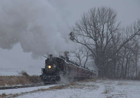 View of An Antique Restored Steam Locomotive Blowing Smoke and Steam Traveling Thru Farmlands and Countryside in a Snow Storm 스톡 콘텐츠