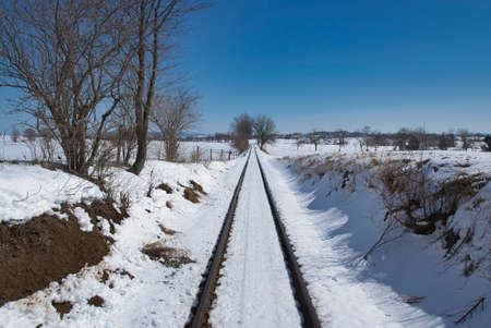 View of Rail Road Tracks Running Thru the Countryside Covered in Snow 스톡 콘텐츠