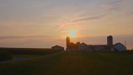 View of a Sunrise Looking over an Amish Farm with Farm House Barn and Silos