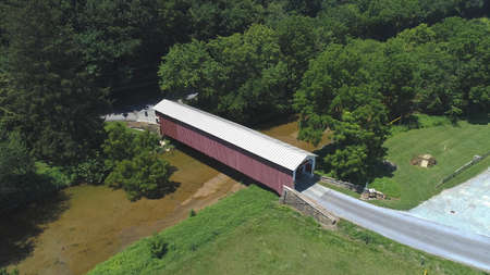 Aerial View of a Covered Bridge in the Pennsylvania Countryside on a Sunny Day 스톡 콘텐츠