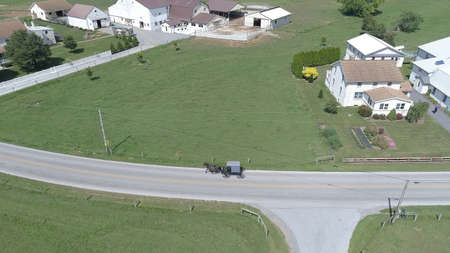 Aerial View of an Amish Horse and Buggy Trotting Along the Road Side