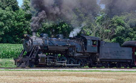View of an Antique Restored Steam Passenger Train Blowing Smoke and Steam on a Sunny Summer Day Archivio Fotografico
