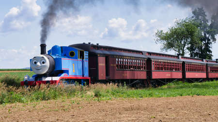 Ronks, Pennsylvania, June 2019 - Thomas the Tank Engine Approaching Pulling Passenger Cars Blowing Smoke on a Beautiful Sunny Day