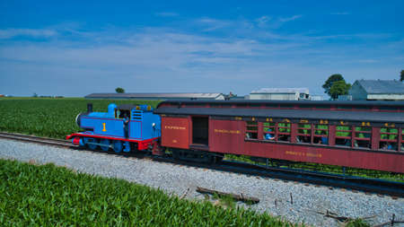 Ronks, Pennsylvania,June 2019 - Aerial View of Thomas the Tank Engine Approaching Thru Trees and Farmlands Pulling Passenger Cars Blowing Smoke on a Beautiful Sunny Day