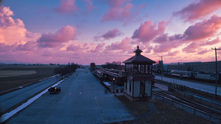 Sunrise With Blue, Red Sky and Clouds Looking Over a Train Station and Yard