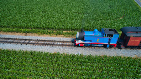 Ronks, Pennsylvania, June 2019 - Aerial View of Thomas the Tank Engine Approaching Pulling Passenger Cars Blowing Smoke on a Beautiful Sunny Day Editoriali