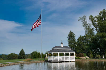 View of a Pond and Gazebo With an America Flag on a Beautiful Day