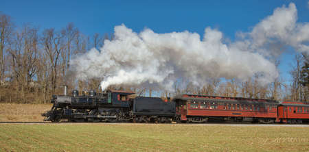 View of an Antique Restored Steam Passenger Train Blowing Smoke and Steam on a Sunny Winter Day
