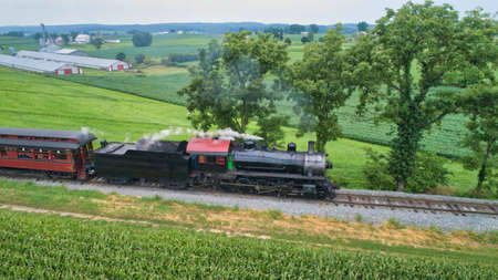 Aerial View of a Steam Locomotive Traveling Across a Fertile Farmland Landscape Blowing Smoke on a Beautiful Summer Day Archivio Fotografico