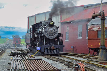 View of An Antique Steam Locomotive Warming Up Blowing Steam and Smoke on an Early Spring Morning Archivio Fotografico