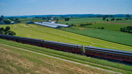 Aerial View of Restored Antique Passenger Train Coaches Travel Thru the Countryside on a Beautiful Simmer Day