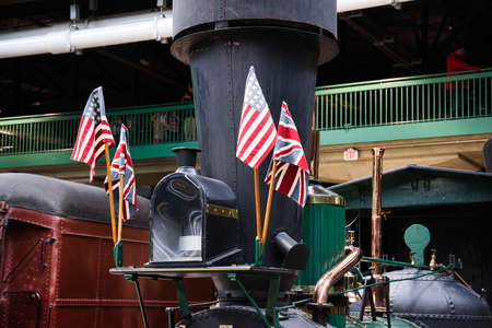 View of An Early Steam Engines Smoke Stack With American and British Flags on it