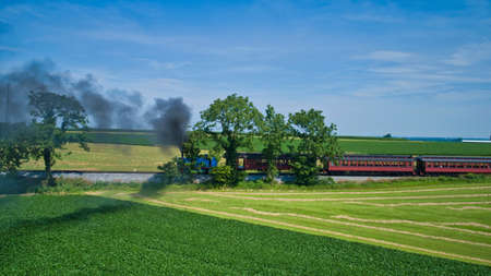 Aerial View of Thomas the Tank Engine Approaching Thru Trees and Farmlands Pulling Passenger Cars Blowing Smoke on a Beautiful Sunny Day Archivio Fotografico