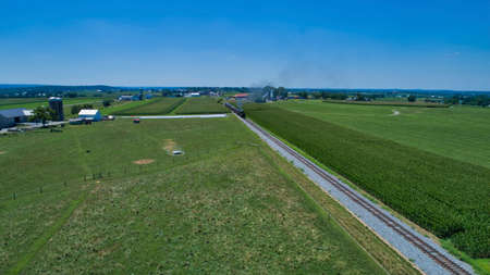 Aerial View of a Steam Locomotive Traveling Across a Fertile Farmland Landscape on a Beautiful Summer Day