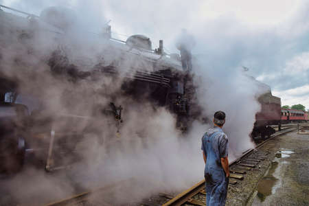 View of An Antique Steam Locomotive Warming Up Blowing Steam and Lots of Smoke on an Early Spring Morning
