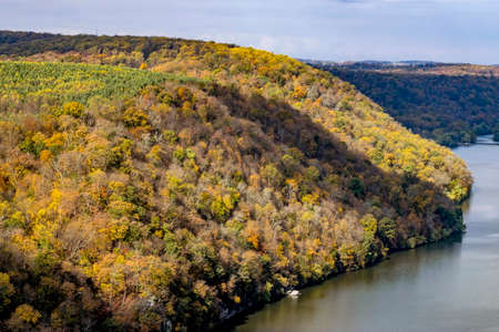 Autumn Foliage Colors in Trees and Farmlands by a River on a Sunny Partly Cloudy Day