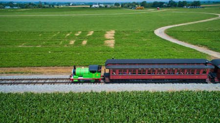 Ronks, Pennsylvania,June 2019 - Aerial View of Percy the Tank Engine Approaching Thru Trees and Farmlands Pulling Passenger Cars Blowing Smoke on a Beautiful Summer Day Editoriali