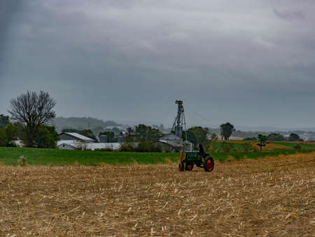 Old Antique Restored Farm Tracker With a Person on it Sitting in a Harvested Field in the Rain
