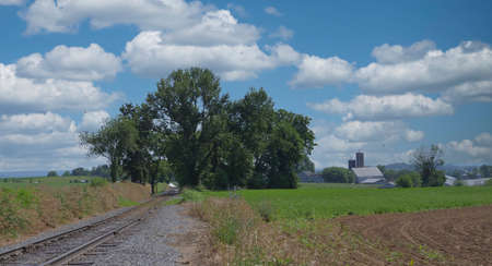 View of a Lonely Rail Road Track Going thru Trees and Farmland on a Sunny Summer Day Archivio Fotografico